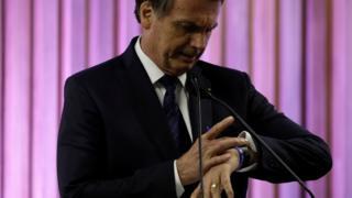 Bolsonaro olha para relógio no pulso durante evento, perto de microfone