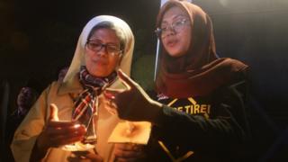 Warga saling membantu menyalakan lilin saat mengikuti aksi solidaritas Malam Seribu Lilin di depan Gereja Katedral, Malang, Jawa Timur, Senin (14/5).