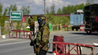 An Indian army man seen standing alert as the Indian army convoys moves on the National Highway on the outskirts of Srinagar.