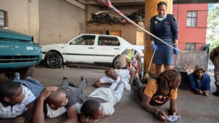 Suspects lie on floor as a member of the South African Police Service (SAPS) arrests them because they defied the lockdown rules and was found with alcohol in Hillbrow, Johannesburg, on March 27, 2020