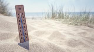 Termômetro em praia, mostrando temperatura alta