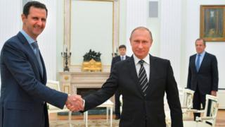 Russian President Vladimir Putin, center, shakes hand with Syrian President Bashar Assad as Russian Foreign Minister Sergey Lavrov, right, looks on in the Kremlin in Moscow, Russia on 20 October