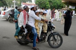 Berapa generasi India di sepeda motor ini -yang sedang menuju sebuah masjid di Hyderabad.