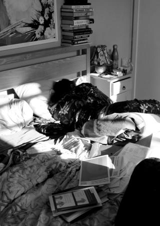 A black-and-white photo of a person lying in bed surrounded by possessions