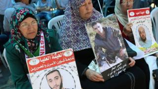 Palestinians in the West Bank city of Ramallah hold pictures of relatives being detained in Israeli jails during a rally calling for the release of Palestinian prisoners in Israel, 18 April 2017.