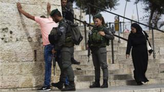 Israeli border policemen perform a security check on a Palestinian youth at Damascus Gate just outside Jerusalem's Old City before Friday prayers on 23 October 2015