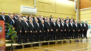 Caldicot Male Voice Choir standing together at a performance