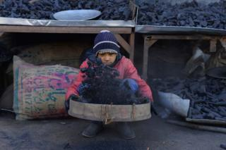 A young vendor sifts charcoal at his stall in Herat, Afghanistan