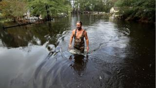 Man wades through thigh-high floodwater in neighbourhood