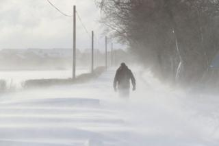 A man walking in snowy conditions in Larbert, Scotland