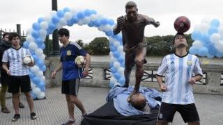 Youths play with footballs next to a sculpture of Argentina's forward Lionel Messi, after it unveiling by Buenos Aires Mayor Horacio Rodriguez Larreta in Buenos Aires, Argentina, on June 28, 2016