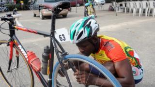 Un cycliste Béninois réparant son vélo lors du tour international cycliste de la Cedeao à Lagos en 2013 (illustration)