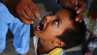 A health worker gives the polio vaccine to a child in Pakistan