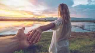 Hombre tomando de la mano a una mujer, que se ve de espaldas.