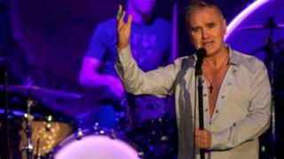 A recent photo of Morrissey during a performance. He is standing at a microphone and singing.