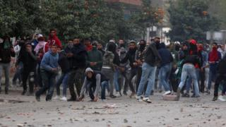 Protesters throw stones during demonstrations against rising prices and tax increases, in Tebourba, Tunisia, January 9, 2018.