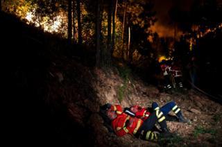 Bomberos toman un descanso en la lucha contra un incendio forestal en Penela, en el centro de Portugal.