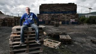 Davy McGrotty watches over the unfinished bonfire in an area known as The Village, in South Belfast.