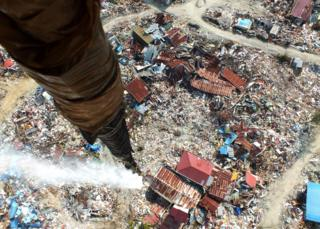 A helicopter releases disinfectant over an area affected by the earthquake in Palu, Indonesia