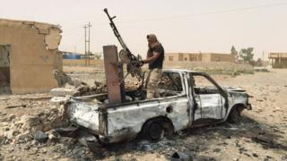 A militiaman allied with the Iraqi security forces dismantles a weapon from a destroyed vehicle belonging to the Islamic State group following a U.S.-led coalition airstrike against IS positions in southern Ramadi, Anbar province, Iraq, Monday, July 20, 2015.