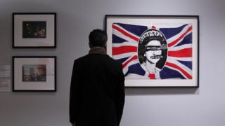 """A man views a work depicting Britiain's Queen Elizabeth II entitled """"God Save The Queen"""" (R) by artist Jamie Reid made for British punk band the Sex Pistols in 1977 during 'The Queen: Art and Image' exhibiton at the Ulster Museum in Belfast, Northern Ireland on January 14, 2012."""