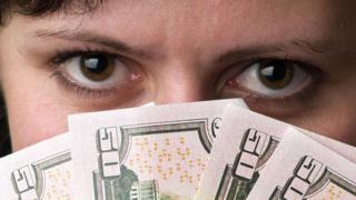Mulher segura notas de dinheiro