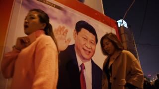 北京市民走在習近平的海報旁。