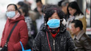 Chinese residents wear masks at a bus station near the closed Huanan Seafood Wholesale Market