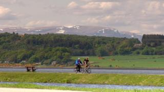 Cyclists alongside Loch Ness in Scotland