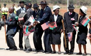 Malawians hold flags as U.S. first lady Melania Trump arrives in Lilongwe, Malawi, October 4, 2018.