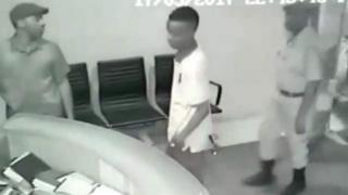 Kamera za CCTV zinamuonyesha mwanamume mwenye kofia akiingia studioni akiwa anasindikizwa na polisi waliojihami