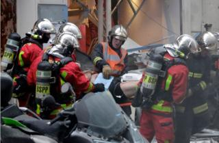 An injured man is evacuated on a stretcher by firefighters