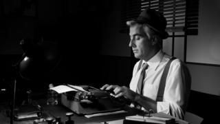 A black and white image of a man typing frantically on a typewriter
