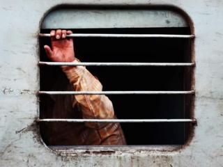 Una mano sale por la ventana de un tren