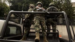 Miembros de las fuerzas federales fuertemente armados en un auto