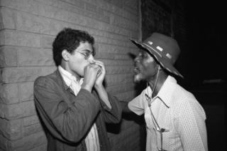 Good Rockin' Charles gives a young French musician a harmonica lesson in the alley outside a club