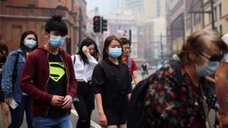 People wear face masks while walking through Sydney