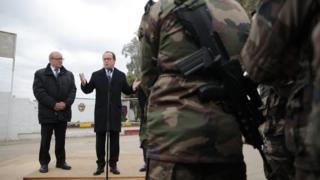 French President Francois Hollande, right, flanked by French defense minister Jean-Yves Le Drian addresses French soldiers at the Iraqi Counter Terrorism Service Academy on the Baghdad Airport Complex in Baghdad, Iraq, Monday, Jan. 2, 2017.