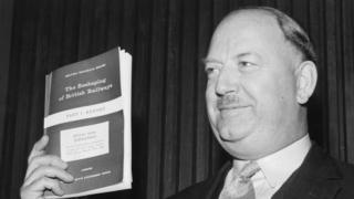 Dr Richard Beeching brandishes a copy of his 1963 report The Reshaping of British Railways
