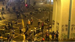 示威者紛紛撤退,留下牆上的塗鴉,滿地狼藉,遠處的警察仍然站在那裏待命。