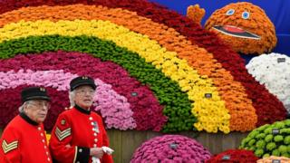 Chelsea Pensioners walk past a floral display at Chelsea Flower Show
