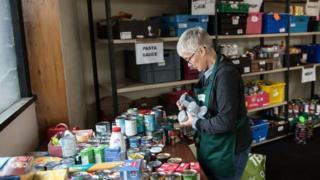 woman stacking cans at food bank