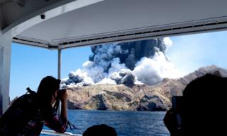 Tourists on a boat witnessing and taking photos of the volcano on New Zealand's White Island as it spews steam and ash
