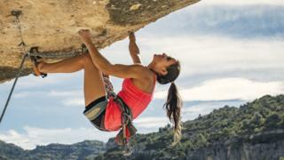 a woman clinging on to a rock face