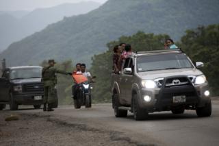 Migránsok a mexikói biztonsági erők ellenőrzési pontján Dél-Mexikóban