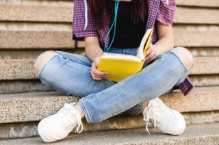 A teenage girl reading a book