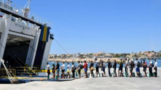 Migrants escorted by Guardia Di finanza police queue to board on a tourists ferry boat to Porto Empedocle in the Italian Pelagie Island of Lampedusa on July 29, 2020. - Boats with migrants mainly from Tunisia continue to arrive on the Italian island of Lampedusa. Intercepted by the boats of the Italian costal guard and guardia di finanza police before reaching the shore, migrants are escorted on the Island and transferred to the island's reception centre.