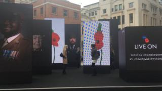 People walking around the Royal British Legion's 'rethink Remembrance' video installation in London.