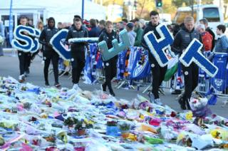 Leicester City players led by goalkeeper Kasper Schmeichel (right) bring individual wreaths to add to the tributes at Leicester City Football Club.