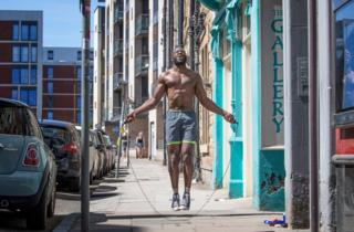 in_pictures A man jumps over a skipping rope in a street